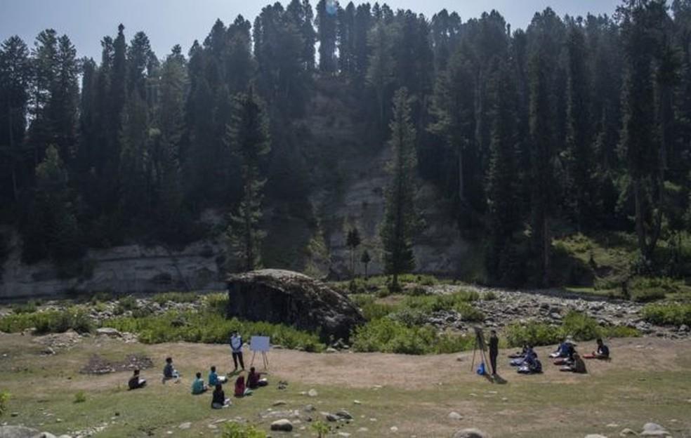 Na Caxemira, crianças estudam ao ar livre, mesmo sob condições climáticas imprevisíveis - uma vez que a 'nova sala de aula' fica aos pés da cordilheira do Himalaia — Foto: BBC