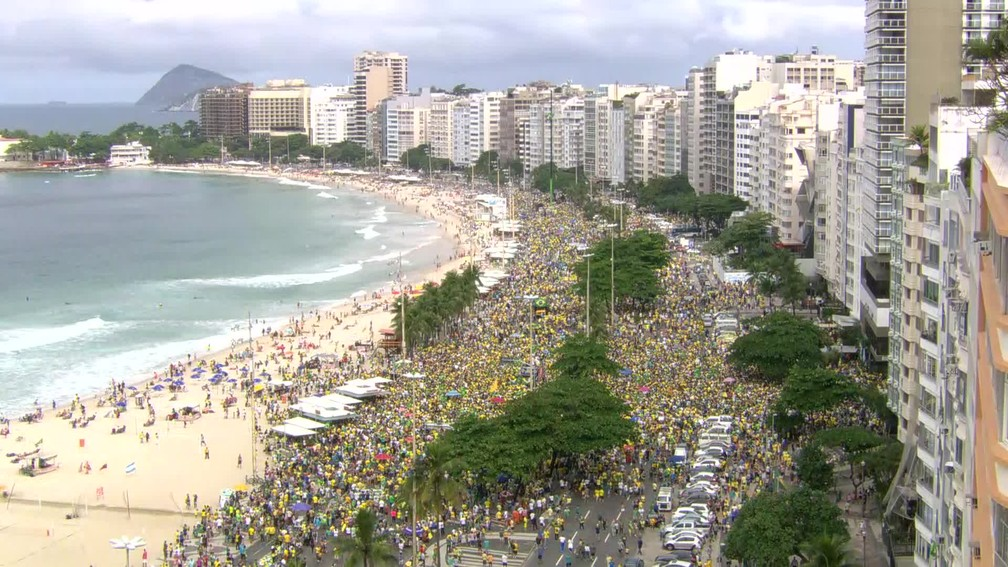 RIO DE JANEIRO, 12h: Por volta das 12h, manifestantes ocupavam cerca de 7 quarteirões da Praia de Copacabana neste domingo (26) — Foto: Reprodução/GloboNews