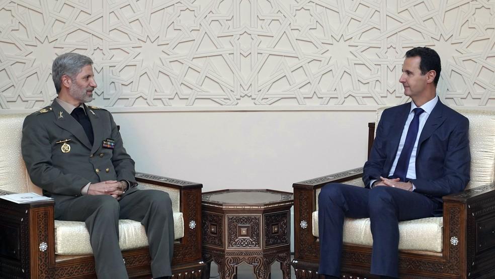Ministro da Defesa do Irã, Amir Hatami, e o presidente sírio, Bashar al-Assad, se reúnem neste domingo (26) em Damasco (Foto: SANA via AP)