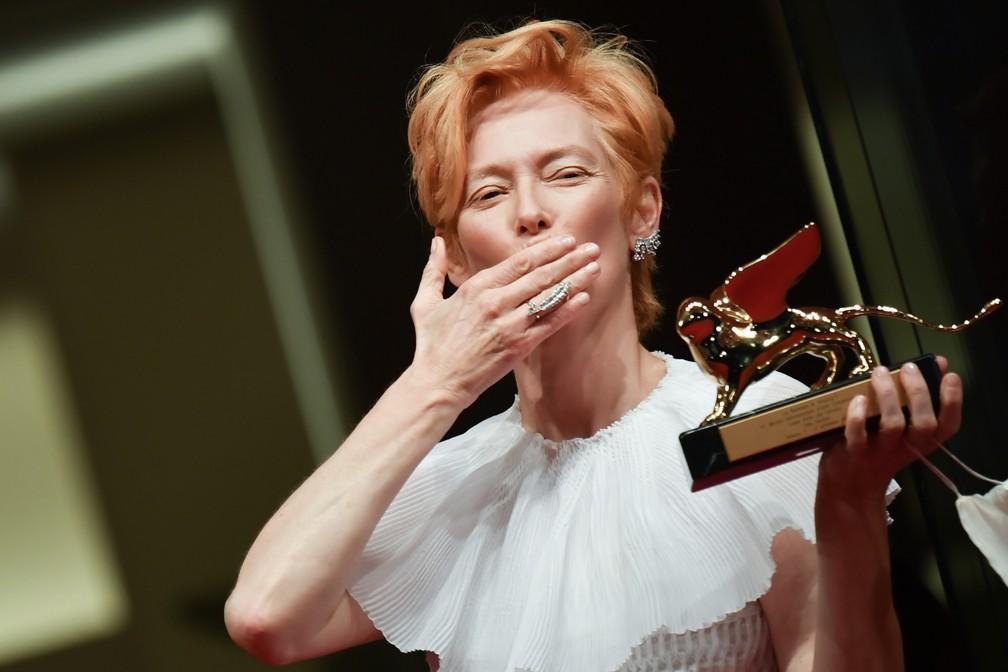 Sem máscara facial, a atriz britânica Tilda Swinton manda um beijo enquanto posa no tapete vermelho após receber o prêmio Leão de Ouro pelo conjunto da obra durante a cerimônia de abertura do 77º Festival de Cinema de Veneza — Foto: TIZIANA FABI / AFP
