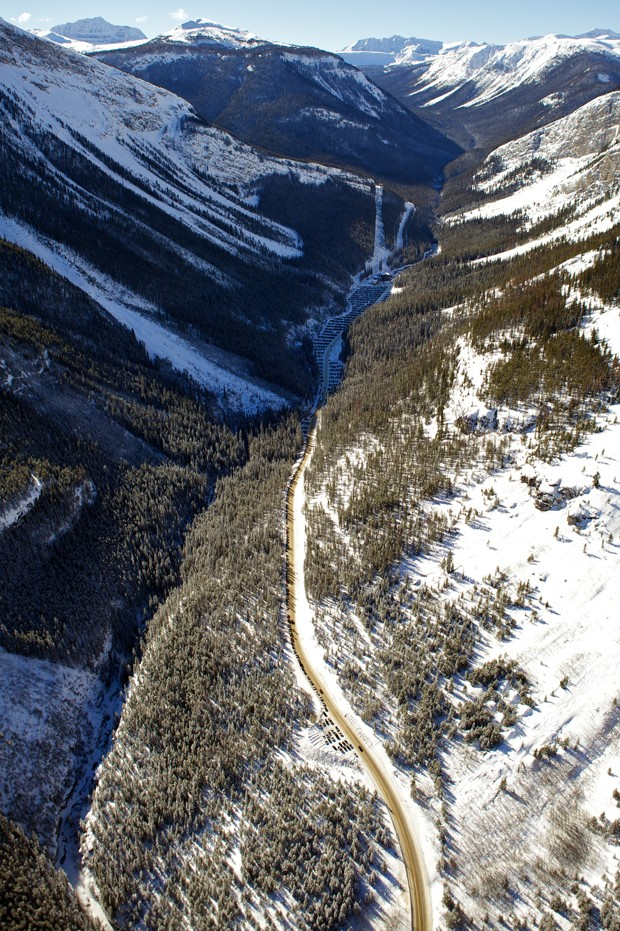 Helicopter aerial view of Access Road, Parking, Base Lodge, Healy Creek and Ski Out at Sunshine Village Ski Resort with blue sky and full snow coverage on Rocky Mountains across the continental divide. (Foto: Getty Images/iStockphoto)