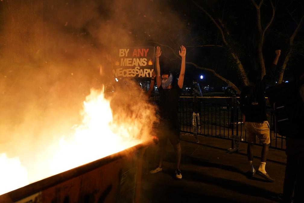Manifestantes incendeiam caçamba de lixo em Washington, perto da Casa Branca, neste sábado (30) novo dia de protestos nos EUA — Foto: Evan Vucci/AP Photo