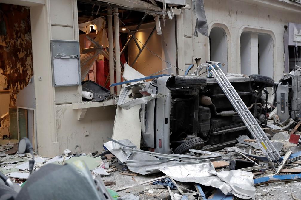 Veículo derrubado é fotografado em meio a destroços após explosão em padaria em Paris, neste sábado (12)  — Foto: Thomas Samson / AFP