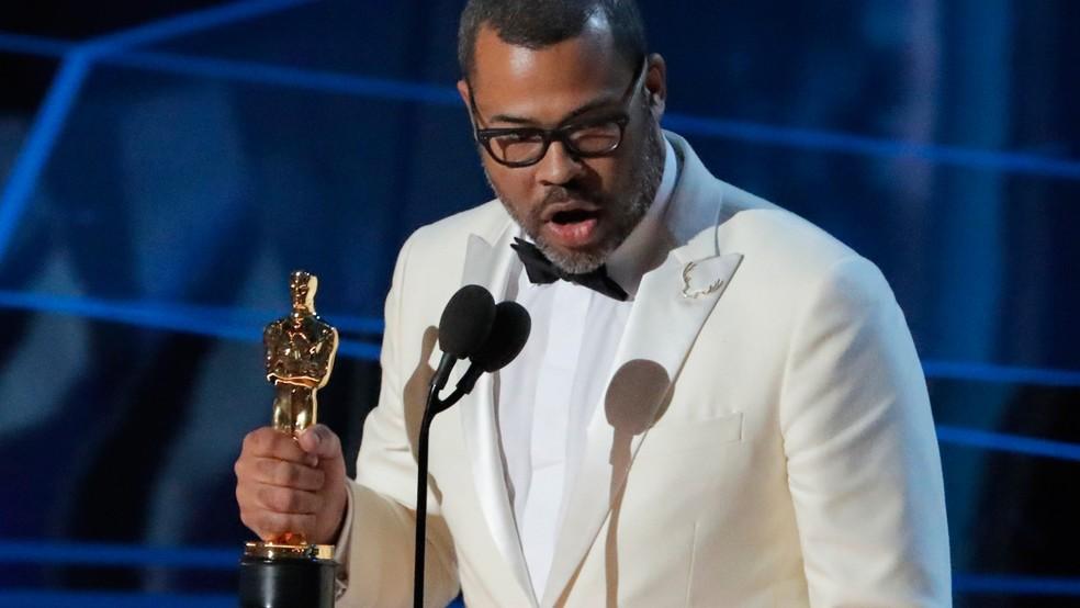 Jordan Peele levanta estatueta do Oscar 2018 por Melhor Roteiro Original (Foto: Lucas Jackson/Reuters)