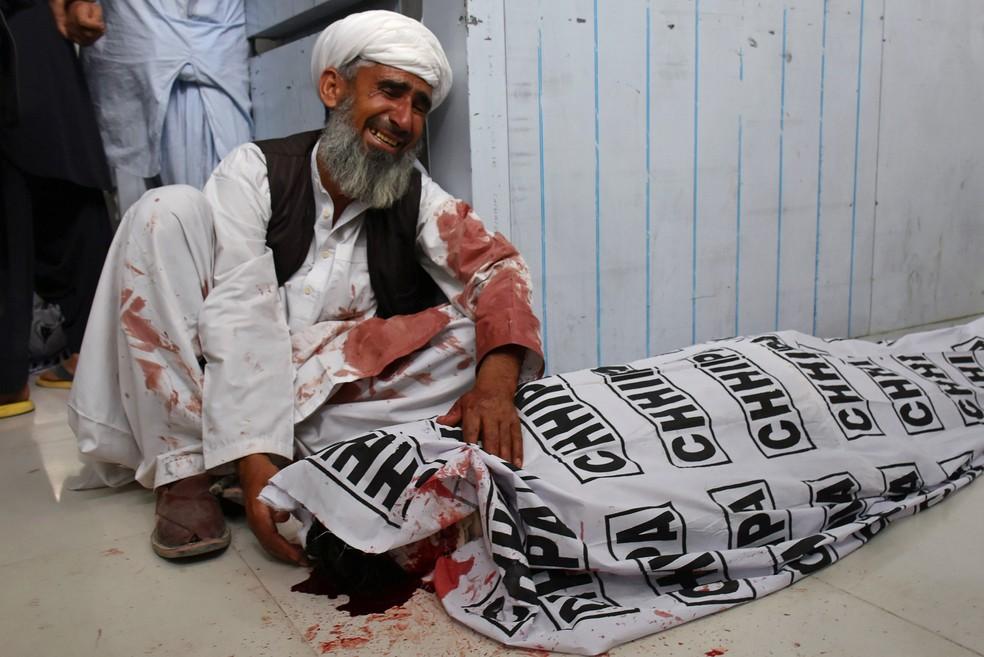 -  Homem chora ao lado de corpo de parente morto em ataque durante um comício, no Paquistão, nesta sexta-feira  13   Foto: Naseer Ahmed/Reuters