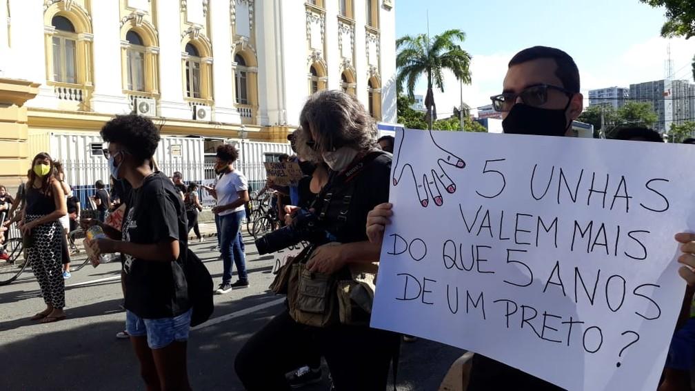 Cartaz lembra o fato de patroa da mãe de Miguel Otávio estar fazendo a unha quando o menino foi para o elevador, antes e cair do 9º andar — Foto: Antonio Coelho/TV Globo