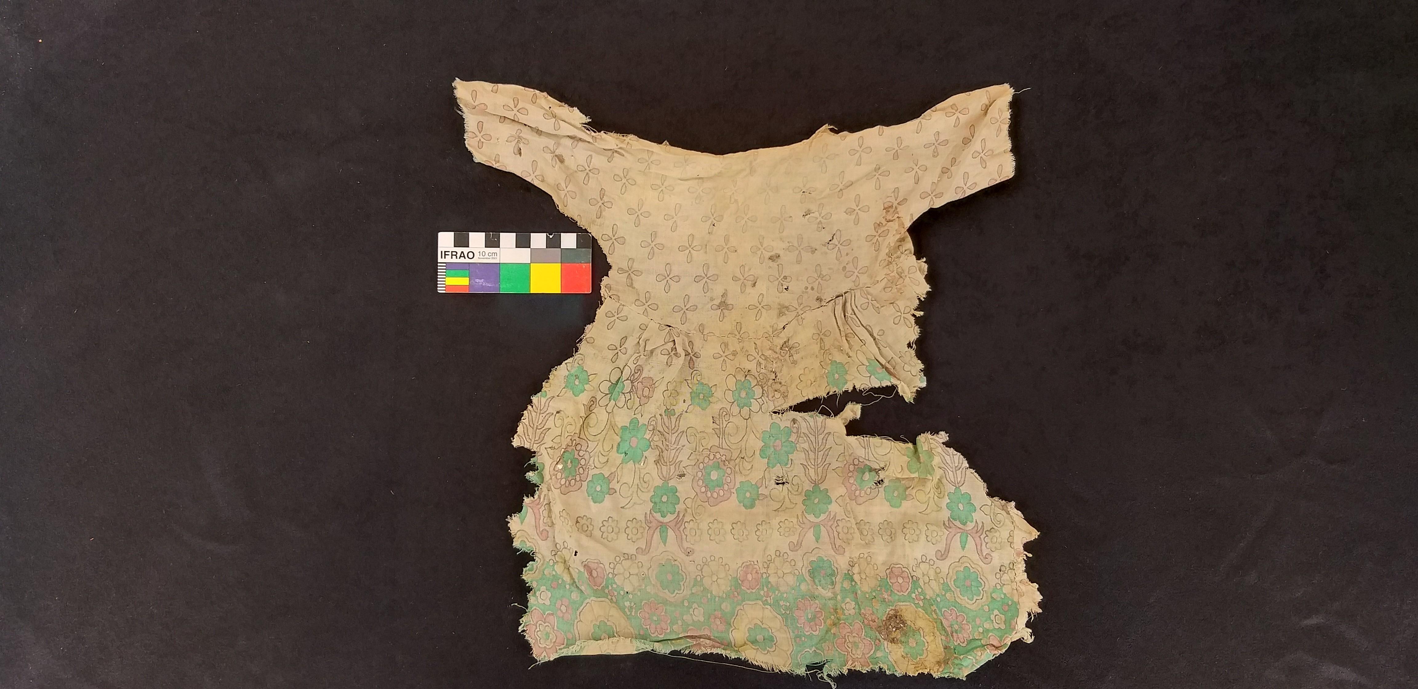 Vestígios de um vestido de criança que também revela a história da ocupação da tumba pela população árabe local (Foto: Divulgação)