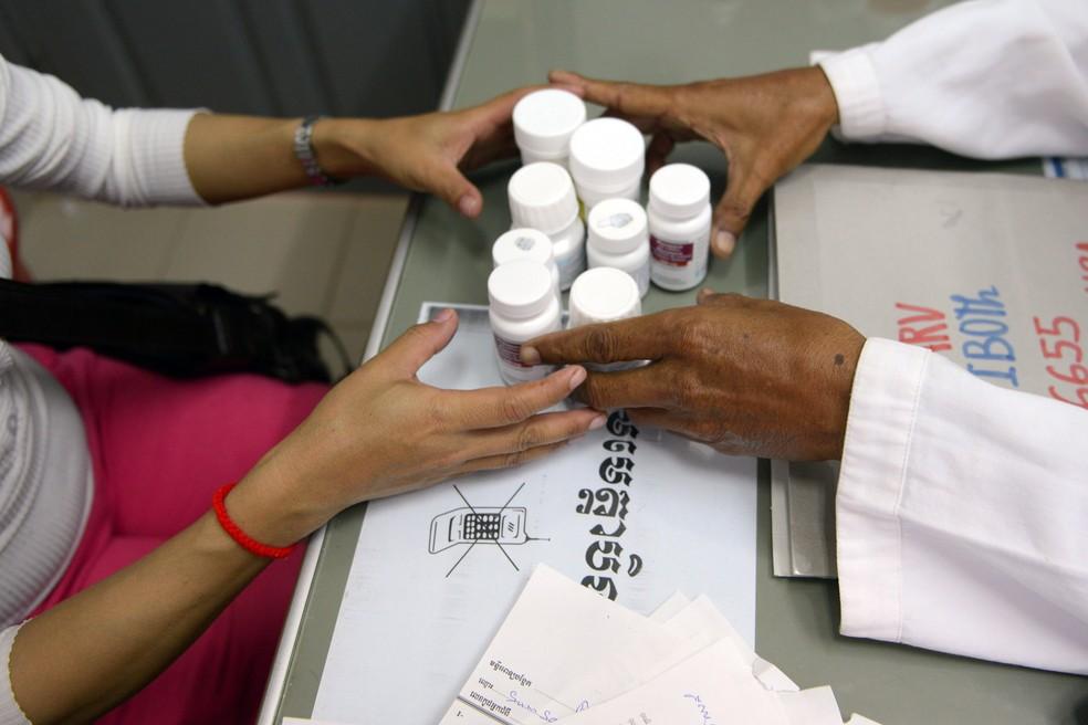 Foto de arquivo mostra um médico (à direita) oferecendo medicamentos antirretroviral para paciente (à esquerda). — Foto: Tang Chhin Sothy/AFP