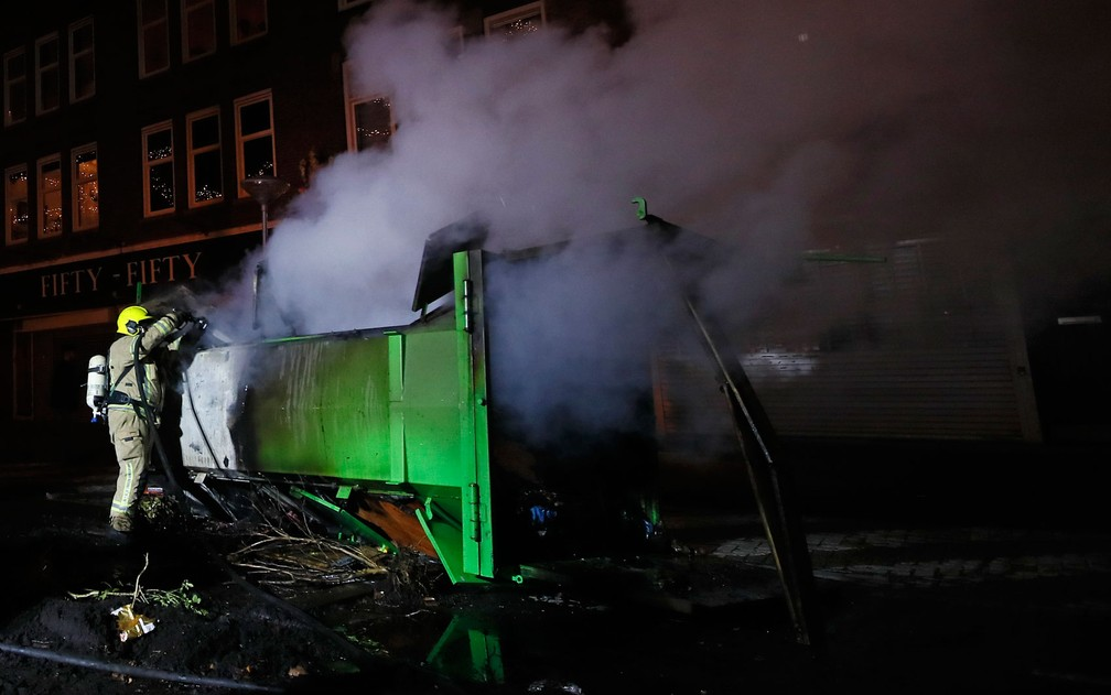 Bombeiro extingue chamas de conteiner de lixo incendiado durante protesto contra toque de recolher em Roterdã, na Holanda, na segunda-feira (25) — Foto: AP Photo/Peter Dejong