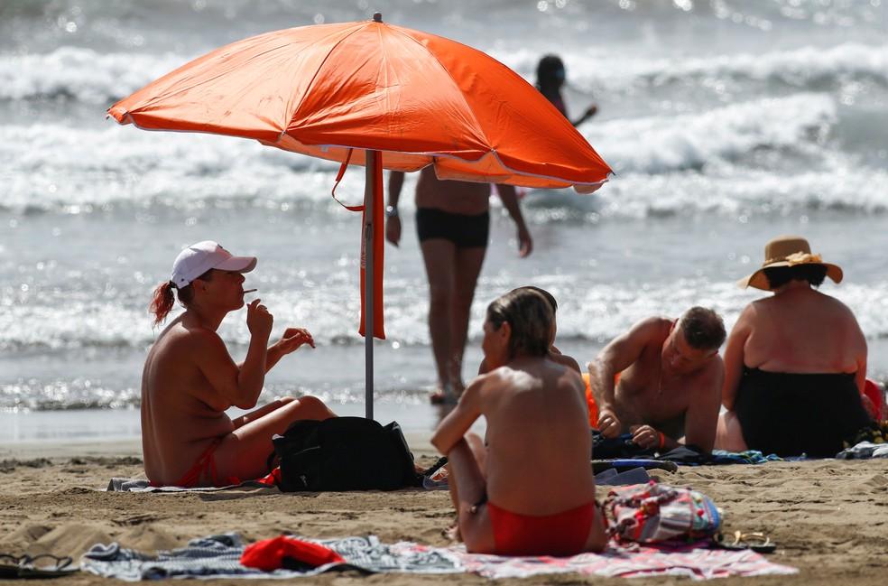 Mulher fuma em praia nas Ilhas Canárias, na Espanha, em agosto de 2020 — Foto: Borja Suarez/Reuters