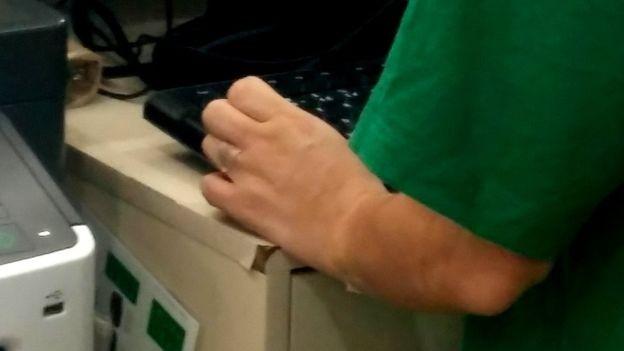 Funcionária da Localiza usa fita micropore no dedo anelar e no antebraço para esconder tatuagem (Foto: Felipe Souza/BBC News Brasil)