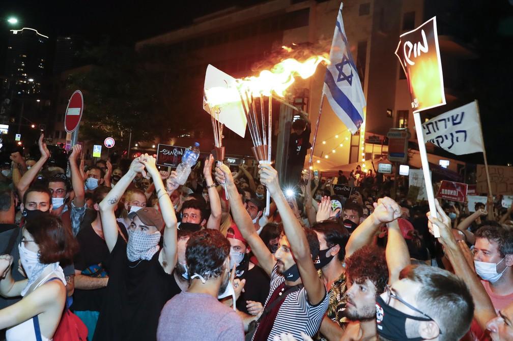 Com máscaras, manifestantes vão às ruas em Tel Aviv, em Israel, para criticar promessas descumpridas por Benjamin Netanyahu durante a pandemia da Covid-19 — Foto: JACK GUEZ / AFP