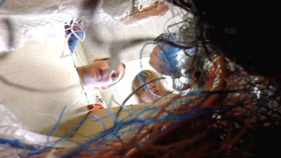 Equipe observa alguns dos itens de plástico coletados pela engenhoca — Foto: BBC