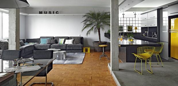 A cozinha é totalmente integrada à sala no apartamento do arquiteto Diogo Oliva. Os espaços são delimitados apenas pelo piso: tacos na parte social e cimento queimado e pastilhas pretas nas áreas molhadas. O amarelo quebra a seriedade da decoração. (Foto: Victor Affaro/Casa e Jardim)
