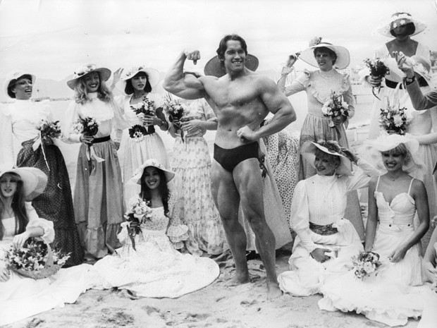 Arnold Schwarzenegger, the film actor who first became famous as Mr Universe for his magnificent physique, on Cannes beach during the Film Festival with the girls from the Folies Bergere.    (Photo by Keystone/Getty Images) (Foto: Getty Images)