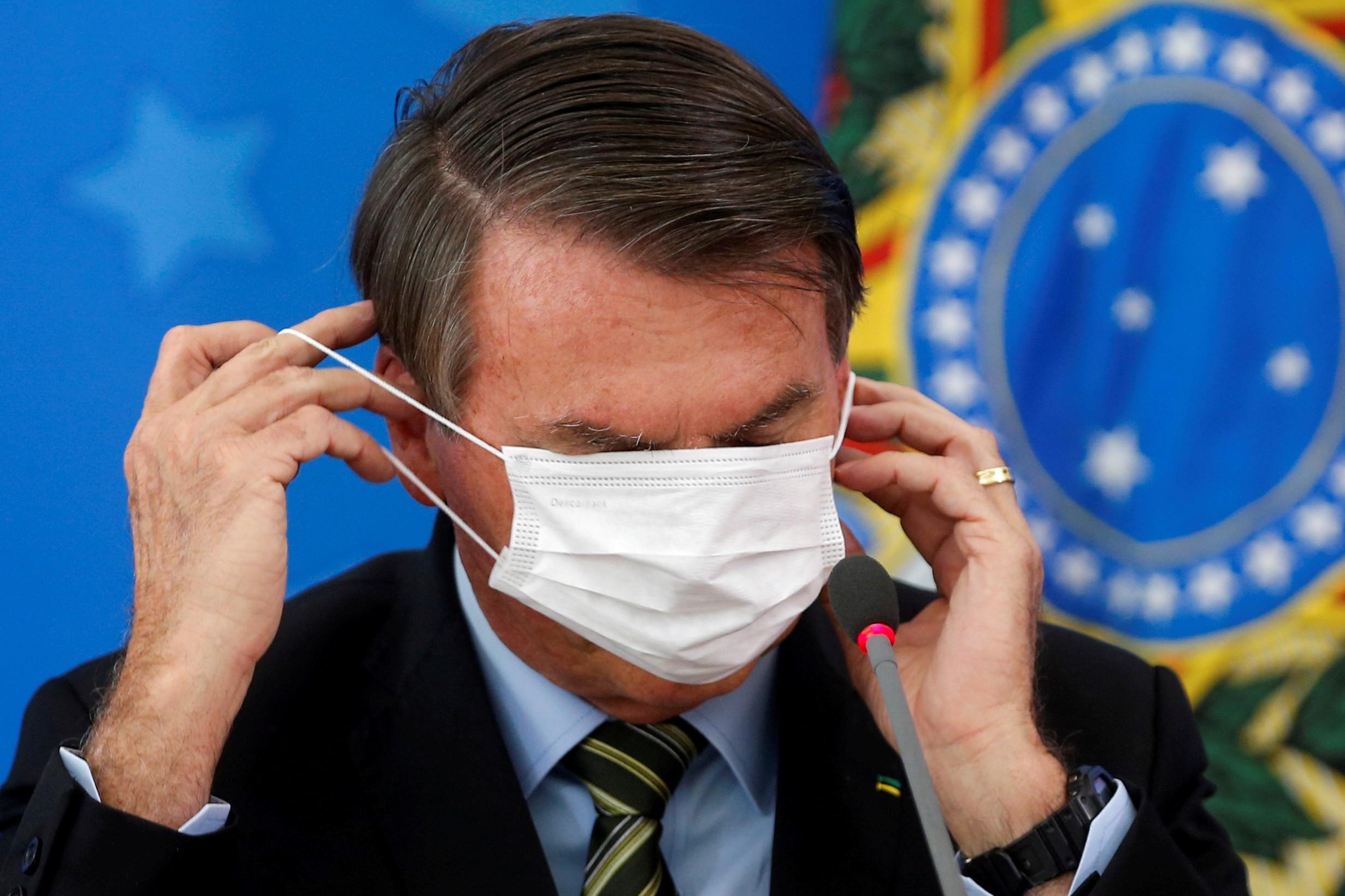 Bolsonaro se atrapalha com máscara em entrevista sobre o coronavírus