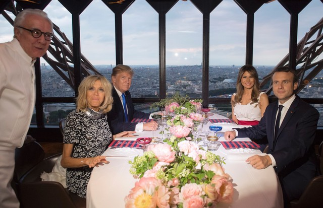 President Donald Trump and Melania Trump (wearing Hervé Pierre) have dinner at the Eiffel Tower at Le Restaurant le Jules Verne (led by chef Alain Ducasse, right), with the French President, Emmanuel Macron, and his wife Brigitte Macron (Foto: AFP/Getty Images)