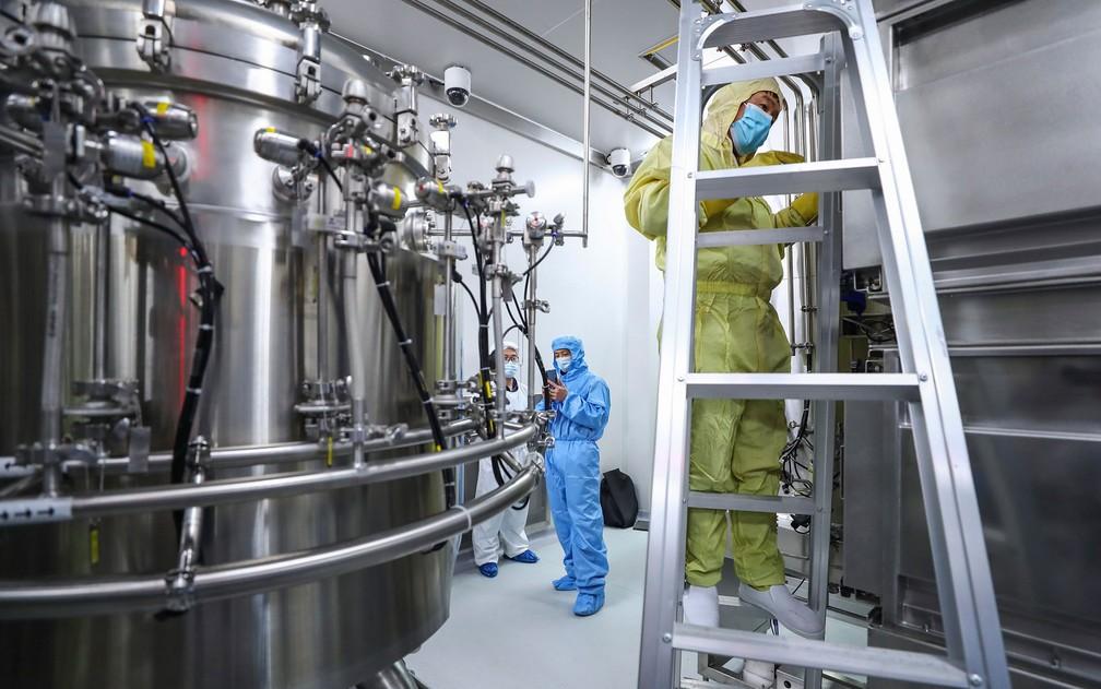 Funcionários checam e limpam equipamentos em fábrica de vacinas da SinoPharm, em Pequim, em foto de 11 de abril — Foto: Zhang Yuwei/Xinhua via AP