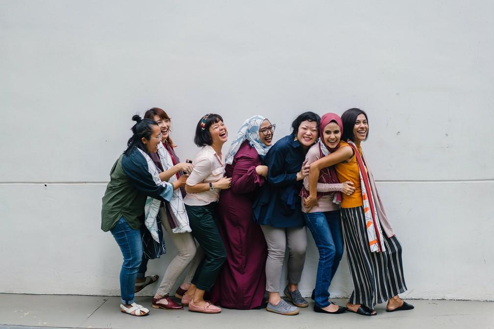 Foto mostra mulheres dando risada e se abraçando enquanto posam para foto.  — Foto: Pexels