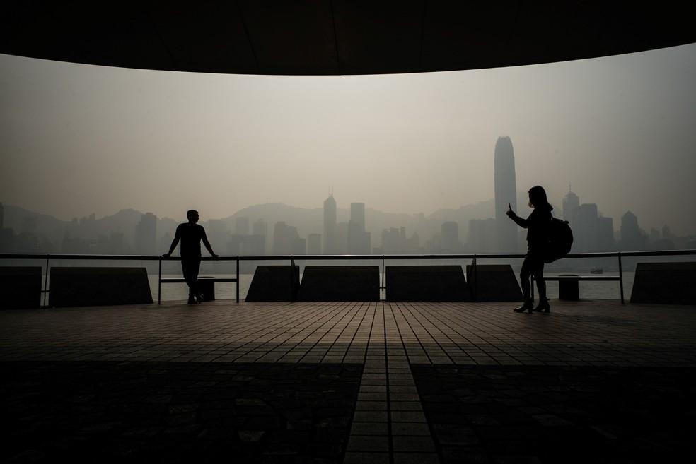 Turistas tiram fotos com a poluição atmosférica tomando o céu do famoso horizonte de Hong Kong. Os meses de inverno trazem regularmente pior qualidade do ar para Hong Kong e outras partes da região devido à direção do vento e às condições climáticas — Foto: Anthony Wallace/AFP