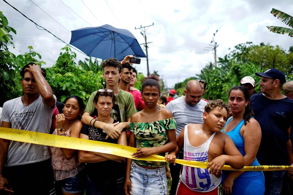 Pessoas observam de longe a ação das equipes de resgate em meio a escombros de avião caído em Havana (Foto: Alexandre Meneghini/Reuters)
