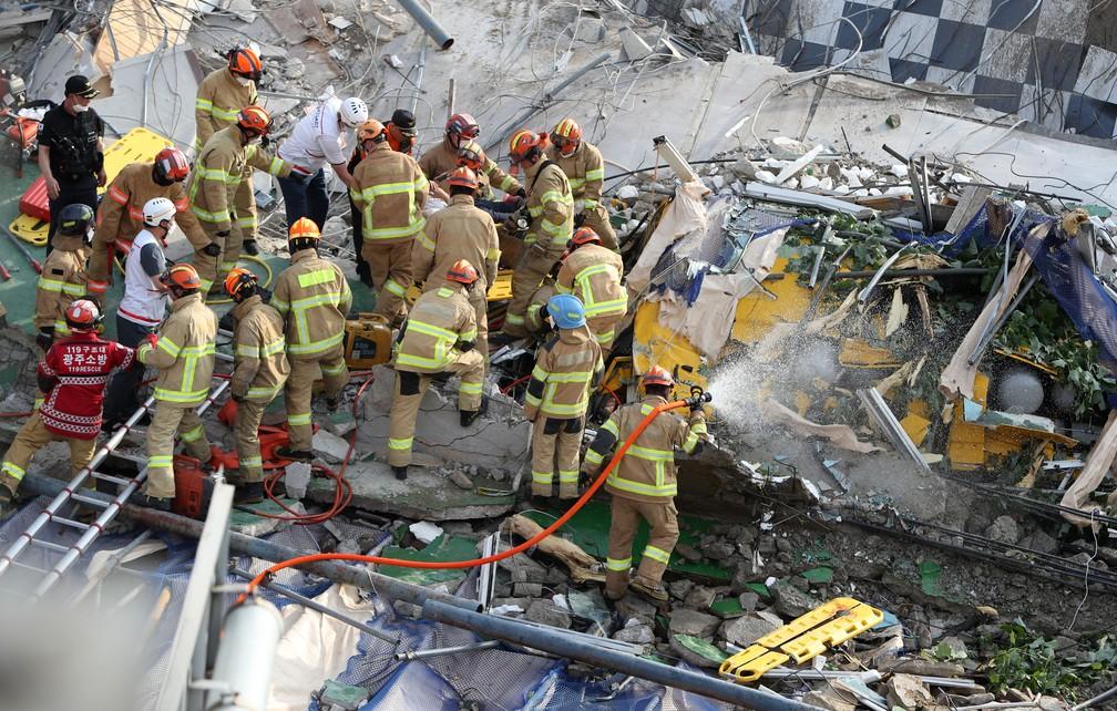 Bombeiros procuram por sobreviventes após prédio desabar em Gwangju, na Coreia do Sul, em 9 de junho de 2021. Edifício estava sendo demolido. — Foto: Yonhap via AP