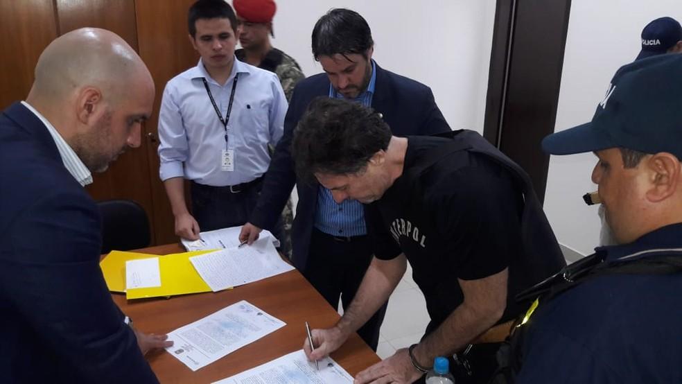 Bruno Farina assina documento pouco antes de ser enviado de volta ao Brasil — Foto: Divulgação/Polícia Nacional do Paraguai