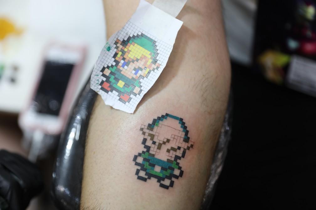 Marine Perrenoud tatua um Link, de 'Zelda', no bancário Tiago Mendonça, de 37 anos, na CCXP 2018 — Foto: Fábio Tito/G1