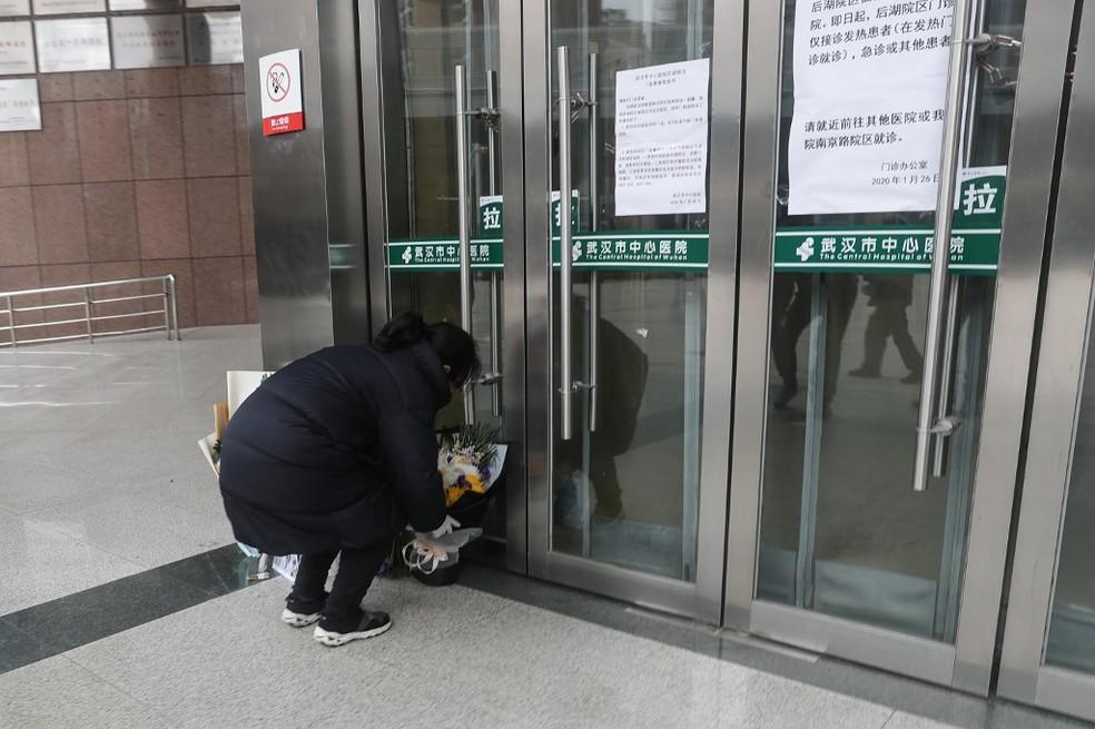 Mulher é vista colocando flores em frente ao Hospital Central de Wuhan, onde o médico oftalmologista Li Wenliang morreu com coronavírus; ele chegou a ser investigado pela polícia por 'espalhar boatos' quando identificou o coronavírus antes da doença se tornar um surto internacional. — Foto: STR/AFP