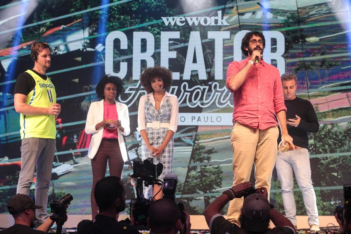 Miguel McKelvey, cofundador da WeWork, Priscila Gama, fundadora da Malalai, Lucy Ramos, Tomás Abrahão, fundador da Raízs (plataforma vencedora na categoria empreendedor), e, ao fundo, Luciano Huck (Foto: Midori de Lucca/WeWork)