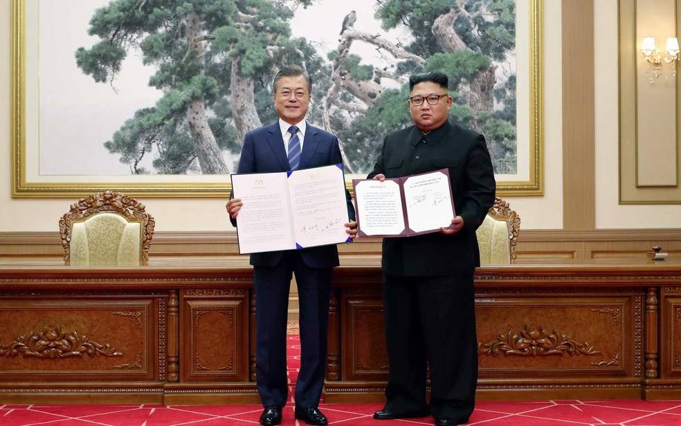 Presidente sul-coreano Moon Jae-in e líder norte-coreano, Kim Jong-un, mostram documento sobre acordo após reunião em Pyongyang, em setembro — Foto: Corpo de Imprensa de Pyeongyang / AFP