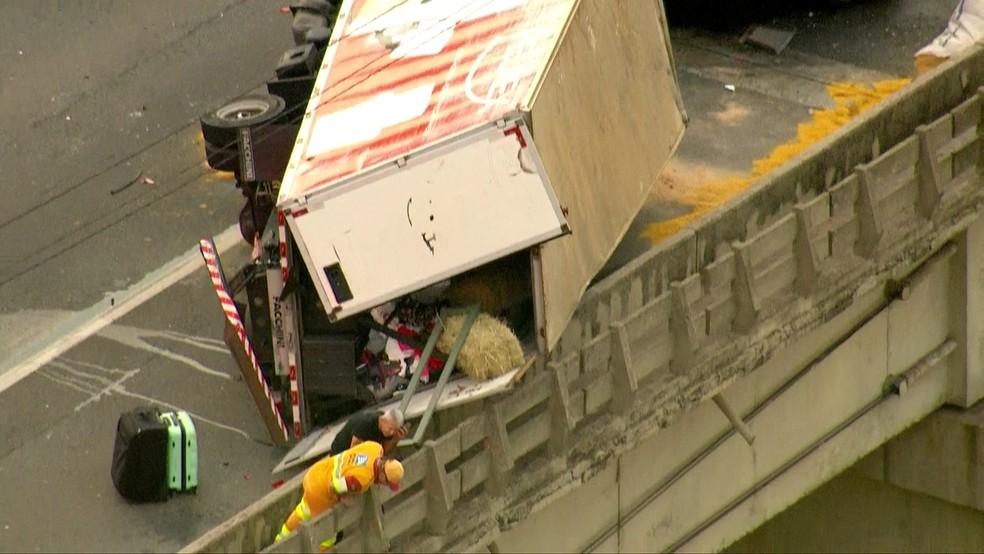 Caminhão tombou no limite da via (Foto: Reprodução/TV Globo)