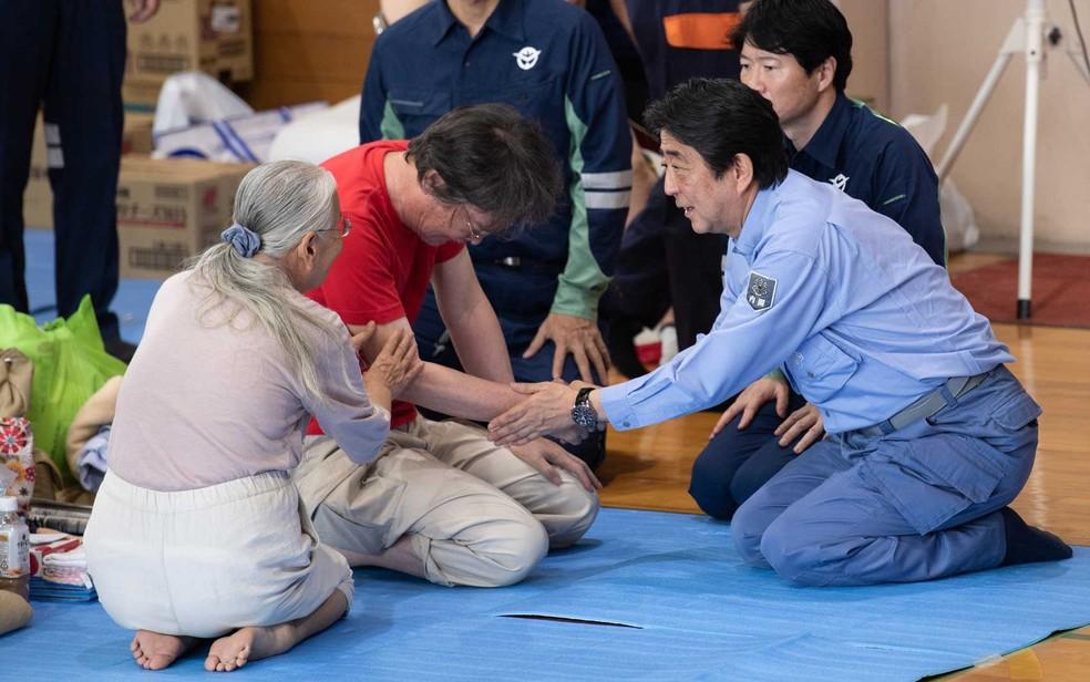O primeiro-ministro do Japão, Shinzo Abe, visita um abrigo para as pessoas afetadas pelas recentes inundações em Mabi, província de Okayama (Foto: Martin Bureau / AFP Photo)