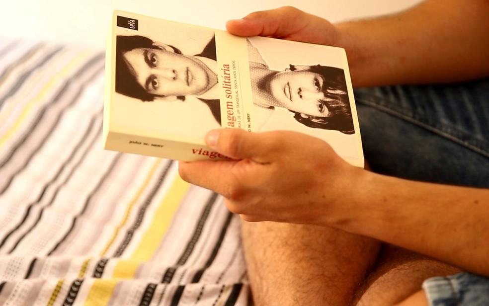 Henrique segura livro 'Viagem Solitária', de João W. Nery, que foi o primeiro transexual a ser operado no Brasil — Foto: Marcelo Brandt/G1