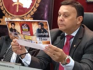 Procurador geral Héverton Aguiar lê folder de divulgação da Expo Show Rodeio (Foto: Gaia Quiquiô/G1)