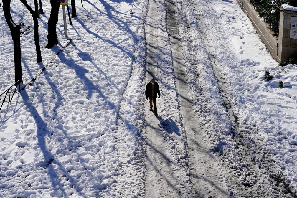 Homem caminha por rua totalmente coberta pela neve em Madrid, nesta segunda-feira (11) — Foto: Juan Medina/Reuters