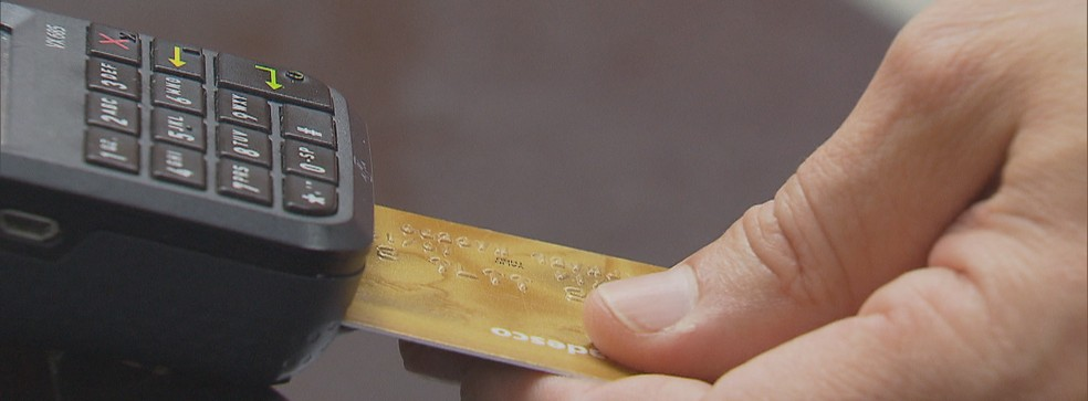 Cliente passa cartão de crédito em máquina de pagamento — Foto: Reprodução / TV Globo