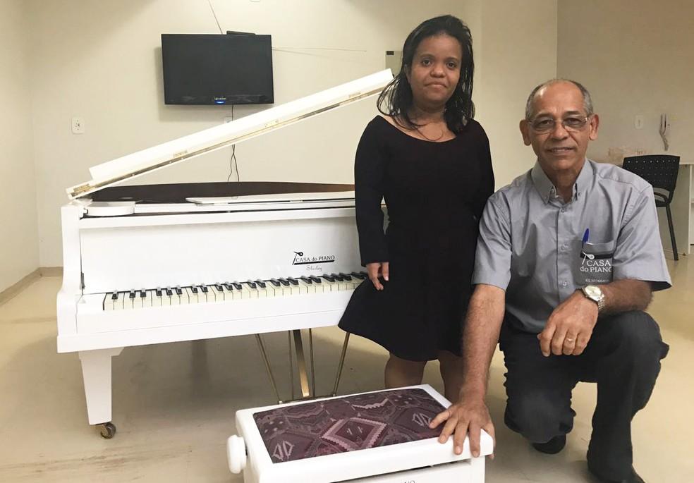 Shirley Nunes ao lado de Rogério Resende, especialista em reformar, afinar e construir pianos, que a presenteou com um instrumento adaptado  (Foto: Letícia Carvalho/G1 )