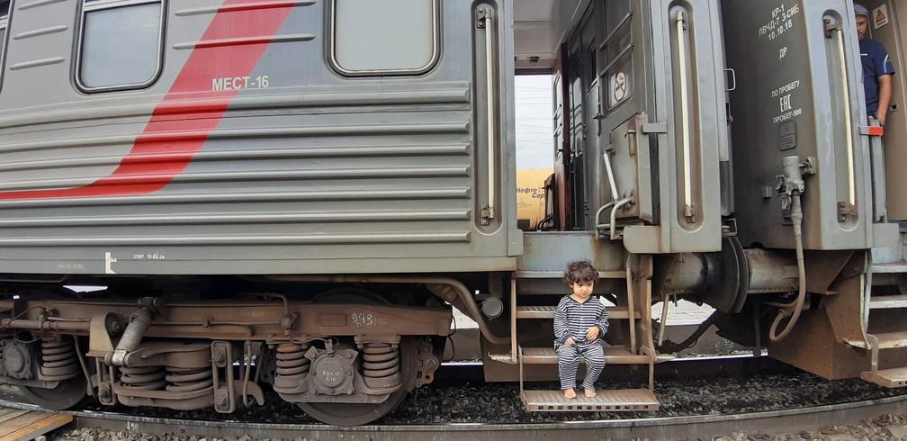 Olívia sentada nas escadas de um dos trens que as duas pegaram para atravessar a Rússia. — Foto: Arquivo pessoal/Gabriela Antunes
