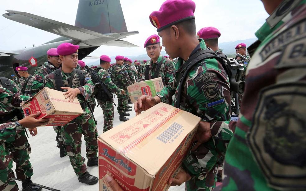 Militares indonésios distribuíram ajuda humanitária no aeroporto de Mutiara Sis Al-Jufri — Foto: Tatan Syuflana / AP Photo