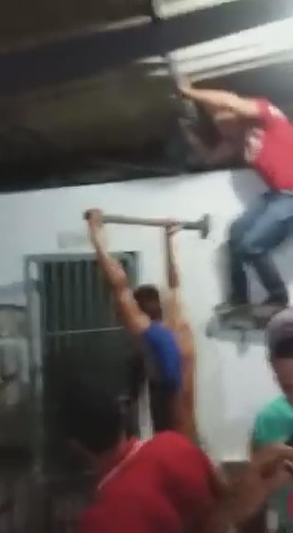 Depois de conseguirem abrir cela, populares comemoram e invadem local para retirar suspeito de homicídios — Foto: Reprodução