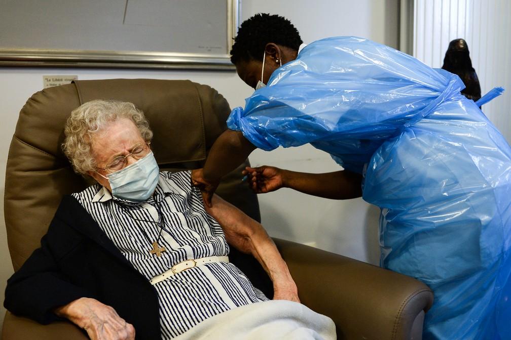 Lucie Danjou, de 101 anos, recebe a primeira dose da vacina da Pfizer/BioNtech contra a Covid-19 em um hospital em Bruxelas, na Bélgica, nesta segunda-feira (28). — Foto: Johanna Geron/Pool/AFP