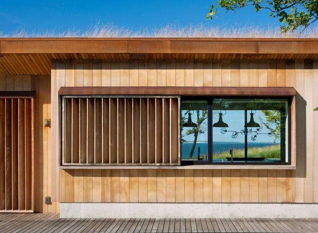 A madeira instalada verticalmente proporciona efeitos de luz e sombra no interior da casa (Foto: Michael Moran/ Reprodução)