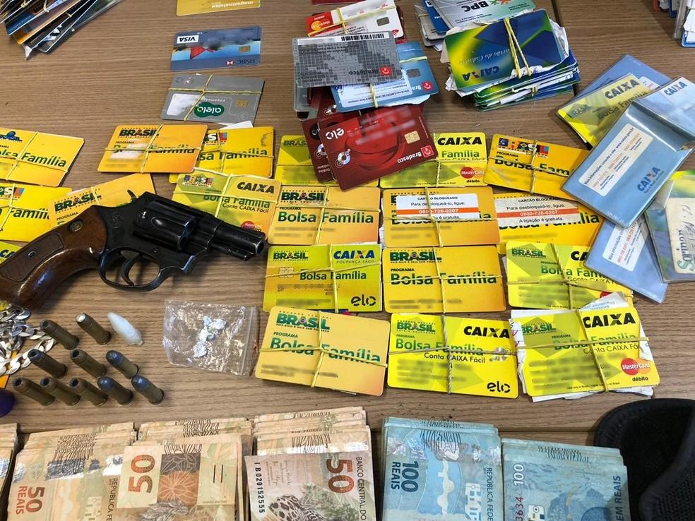 Dinheiro, arma e cartões de benefícios foram apreendidos com suspeito de agiotagem, em João Pessoa — Foto: Walter Paparazzo/G1