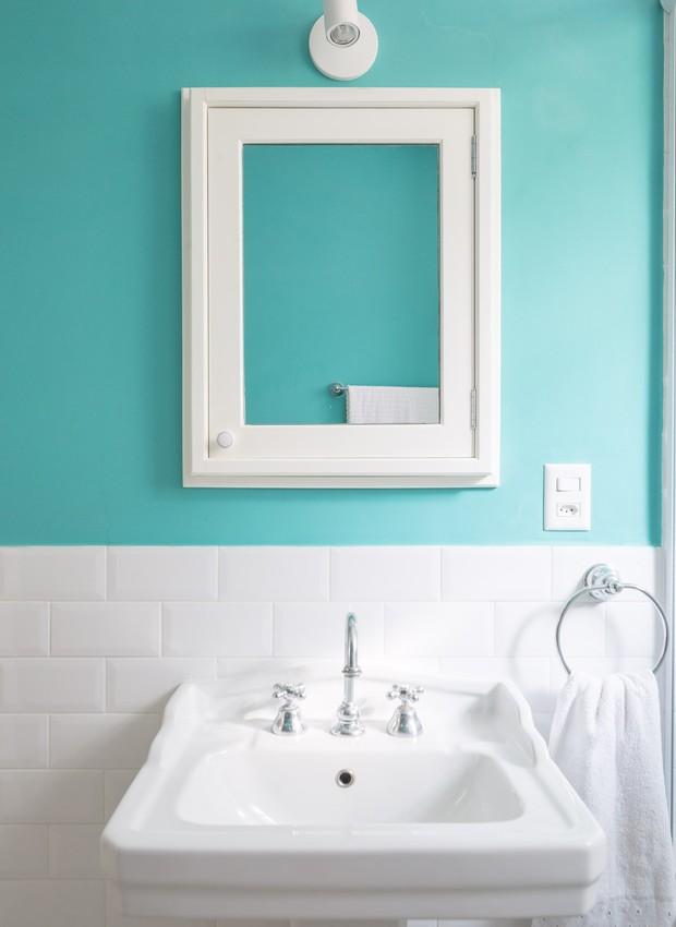 O clima retrô se repete no banheiro do andar de baixo. Ladrilho hidráulico, pia com estilo vitoriano e banheira de imersão fazem contraste com o azul-céu da parede (Foto: Joana França/Divulgação)