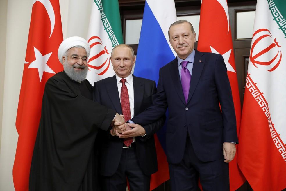 O presidente do Irã, Hassan Rouhani, da Rússia, Vladimir Putin, e da Turquia, Tayyip Erdogan, apertam as mãos nesta quarta-feira (22) durante encontro em Sochi, na Rússia (Foto: Sputnik/Mikhail Metzel/Kremlin via Reuters )