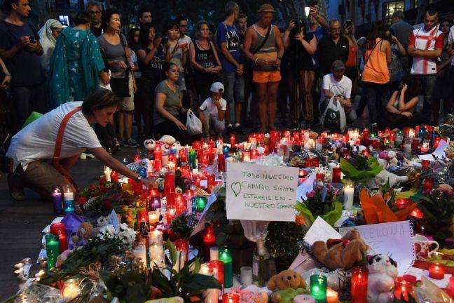 Pessoas deixam flores e velas em homenagens às vítimas em Las Ramblas uma importante via no centro da capital da Catalunha. Ao menos 13 pessoas morreram e mais de 100 ficaram feridas neste ataque, cuja autoria foi reivindicada pelo Estado Islâmico (Foto: Pascal Guyot / AFP / El País)