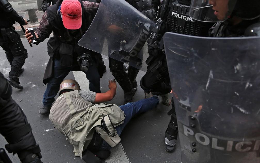 Jornalistas do jornal 'El Comercio' são agredidos por policiais durante protesto contra o aumento dos combustíveis no Equador, em Quito, na quinta-feira (3) — Foto: Cristina Vega/AFP