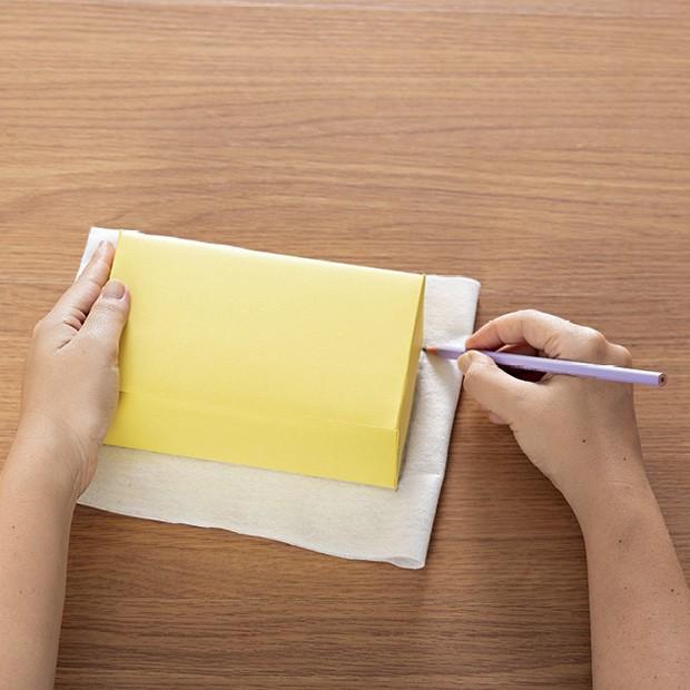 2. Encape as caixas de leite com papel amarelo. Dobre o feltro branco ao meio, marque com lápis o formato da caixa e recorte dois pedaços. (Foto: Bruno Marçal / Editora Globo)