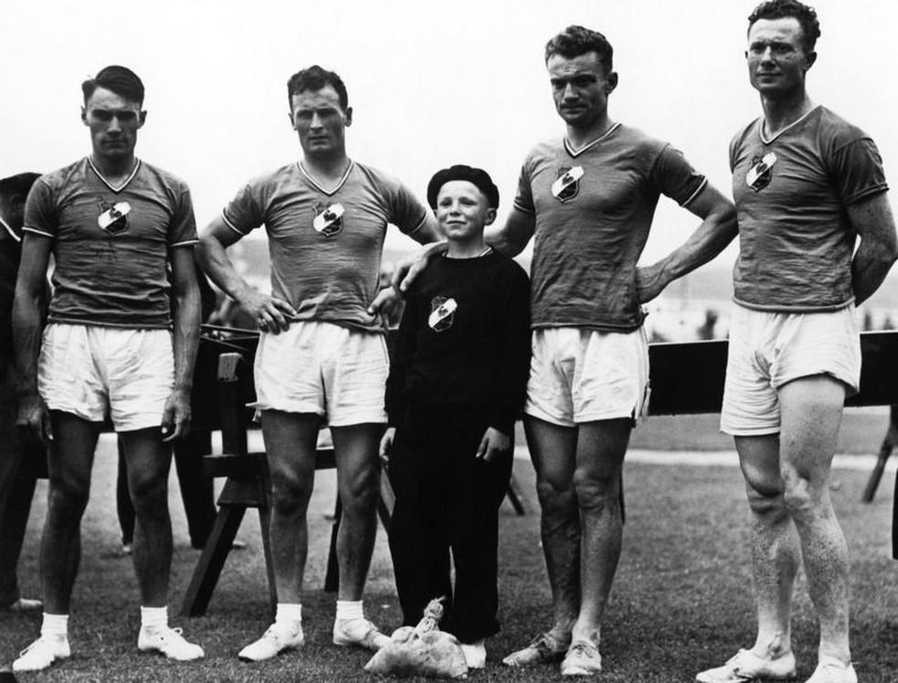 Em 1936, o francês Noël Vandernotte (centro) conquistou 2 medalhas de bronze no remo aos 12 anos de idade. Naquela época, crianças eram colocadas nas equipes para deixar os barcos mais leves. — Foto: Getty Images via BBC